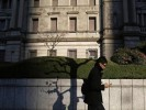 A man using his mobile phone walks past the Bank of Japan headquarters building in Tokyo