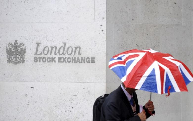A worker shelters from the rain under a Union Flag umbrella as he passes the London Stock Exchange in London, Britain, October 1, 2008. Global stocks and dollar firmer as Trump news conference approaches